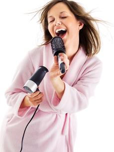 Woman singing with hairbrush,Woman singing with hairbrushの写真素材 [FYI00773808]