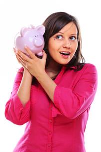 Woman holding pig money-box,Woman holding pig money-box,Woman holding pig money-box,Woman holding pig money-boxの写真素材 [FYI00773921]