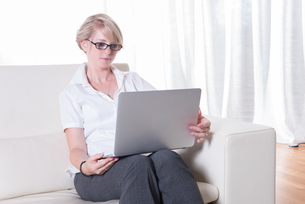 young attractive woman working with laptop on couchの写真素材 [FYI00774266]