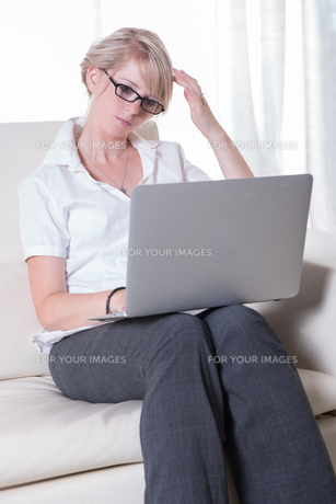 young attractive woman working with laptop on couchの写真素材 [FYI00774273]