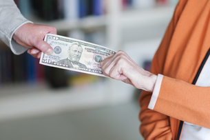 two women pulling on a dollar billの写真素材 [FYI00774348]