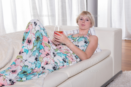 young attractive woman enjoys a cocktail on the couchの写真素材 [FYI00774352]