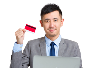 Young businessman holding credit card and computerの写真素材 [FYI00774420]