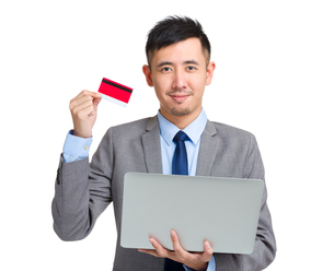 Asian Businessman hold with notebook computer and credit cardの写真素材 [FYI00774444]