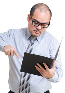Serious Businessman point out something from reportの写真素材 [FYI00774568]
