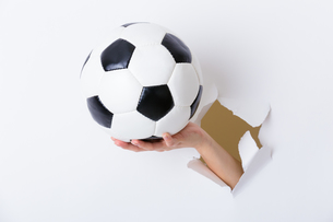 Hand holding soccer ball through the paper holeの写真素材 [FYI00774602]