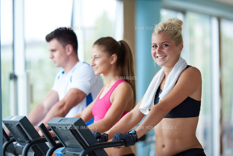 friends  exercising on a treadmill at the bright modern gymの写真素材 [FYI00775289]