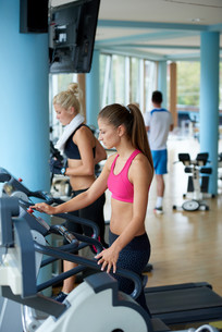 friends  exercising on a treadmill at the bright modern gymの写真素材 [FYI00775303]