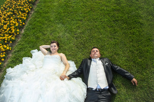 Bride and groom holding hands on lawn with flowersの写真素材 [FYI00775345]