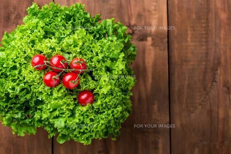 lettuce salad and cherry tomatoes on a wood backgroundの写真素材 [FYI00775885]