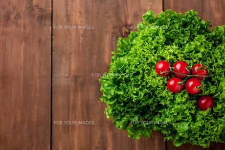 lettuce salad and cherry tomatoes on a wood backgroundの写真素材 [FYI00775894]