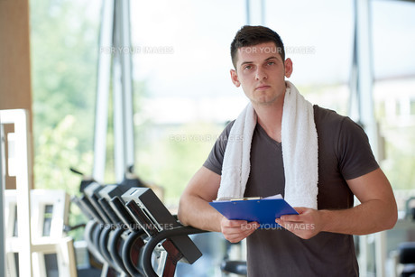 trainer with clipboard standing in a bright gymの写真素材 [FYI00776131]