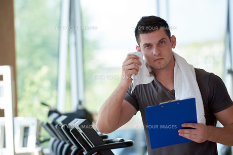 trainer with clipboard standing in a bright gymの写真素材 [FYI00776133]