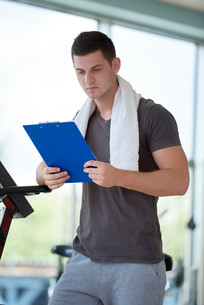 trainer with clipboard standing in a bright gymの写真素材 [FYI00776147]