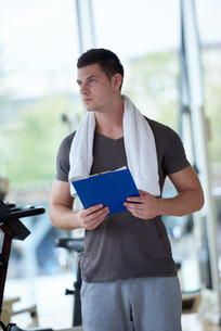 trainer with clipboard standing in a bright gymの写真素材 [FYI00776156]
