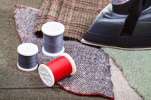 iron and thread spools on fabricsの写真素材 [FYI00776388]