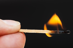 fingers with burning wooden matchの写真素材 [FYI00776452]