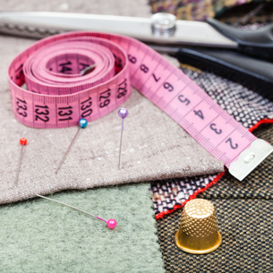 pink measure tape, pins, thimble, shears on tissueの写真素材 [FYI00776460]
