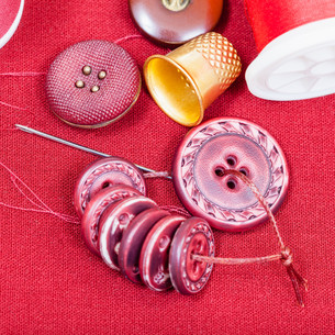 sewing thread, buttons, thimble on red fabricの写真素材 [FYI00776462]