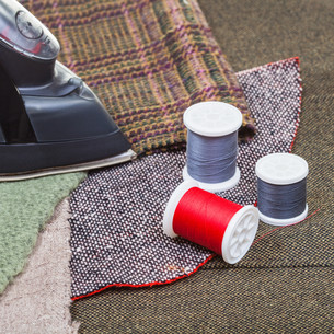 clothing iron and thread spools on textileの写真素材 [FYI00776480]