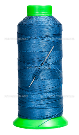 sewing spool with blue thread and attached needleの素材 [FYI00776482]