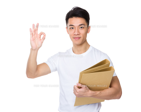 Asian young man hold with folder and ok sign gestureの写真素材 [FYI00776921]