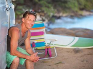 Happy Surfer Sitting at Beachの写真素材 [FYI00777096]
