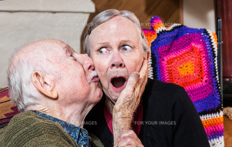 Older Gentleman Kissing Older Woman on Cheekの写真素材 [FYI00777139]