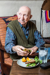Elderly Man Holding Sandwichの写真素材 [FYI00777142]
