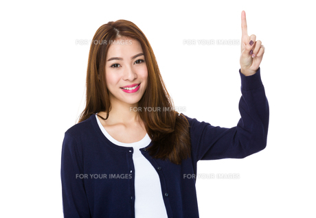 Woman smiling pointing up showing copy spaceの写真素材 [FYI00777230]