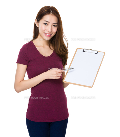 Young cheerful woman with pen and clipboardの写真素材 [FYI00777243]