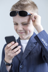 Boy dressed as spy using a smartphoneの写真素材 [FYI00777345]