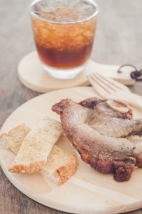Pork steak on wooden plateの写真素材 [FYI00777486]