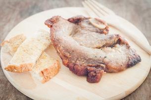 Pork steak on wooden plateの写真素材 [FYI00777497]