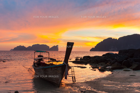 Traditional wooden longtail boat on beach in sunset, Thailand.の写真素材 [FYI00777640]