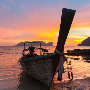 Traditional wooden longtail boat on beach in sunset, Thailand.の写真素材 [FYI00777674]