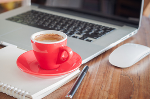 Red coffee cup with notepad and laptopの写真素材 [FYI00777770]