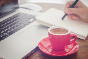 Red coffee cup with notepad and laptopの写真素材 [FYI00777787]