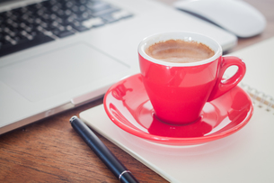 Red coffee cup with notepad and laptopの写真素材 [FYI00777814]