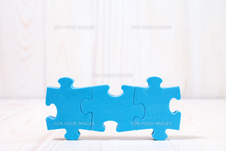 Three puzzle pieces on white wooden backgroundの素材 [FYI00777817]