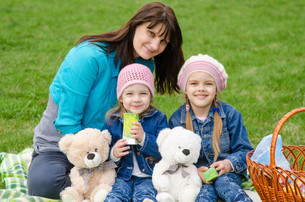 Mum embraces daughters on a picnicの写真素材 [FYI00777881]