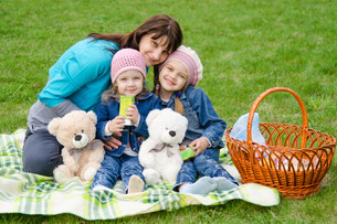 Mum embraces daughters on a picnicの写真素材 [FYI00777898]