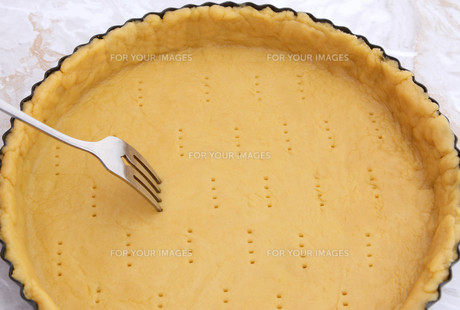 Fork making holes in a raw pastry caseの写真素材 [FYI00777933]