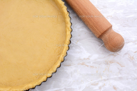 Baking tin lined with pastry, wooden rolling pin besideの写真素材 [FYI00777969]