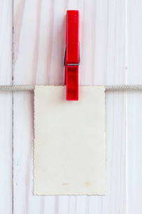 Photo frame hanging over white wooden backgroundの素材 [FYI00778003]