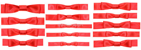 set of red bow knots on narrow satin ribbonsの素材 [FYI00778183]