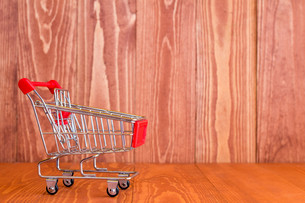 Shopping cart against brown wooden backgroundの写真素材 [FYI00778223]