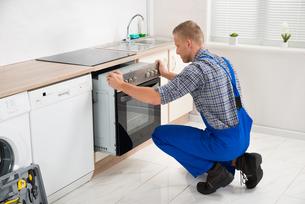 Repairman Repairing Ovenの写真素材 [FYI00778414]