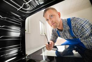 Repairman Fixing Kitchen Ovenの写真素材 [FYI00778423]