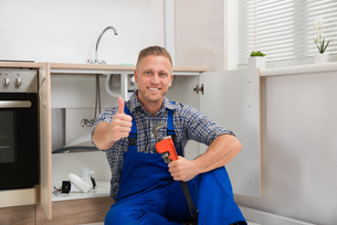 Plumber With Adjustable Wrench In Kitchen Roomの写真素材 [FYI00778426]